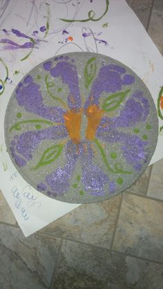 Foot print flower on a stepping stone. Use craft paint and let dry. Spray two coats of clear spray paint to seal.