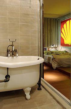 Do banheiro avista-se o dormitório, que tem um luminoso de posto de gasolina