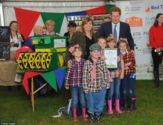 Winning ways: Prince Harry poses with a group of pint-sized prize winners in front of a mo...