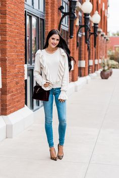 Cream ruffle sweater, skinny jeans, velvet handbag and leopard pumps.
