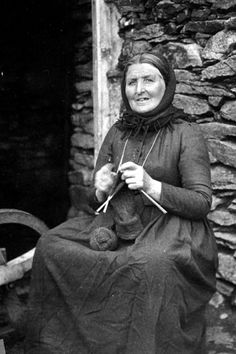 Janet Peterson of Sloag, sitting knitting socks. Shetland, 1902