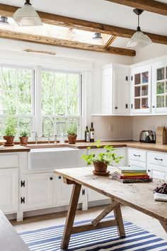 Bright eat-in kitchen with butcher block countertops, wood beams and a skylight.