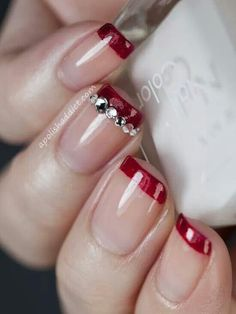 Red french tips with rhinestones on middle finger.