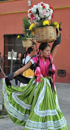 Beautiful ladies carry baskets of flowers on their heads.  This is a familiar sight in the city of Oaxaca where parades and processions like this occur frequently. Happy Easter