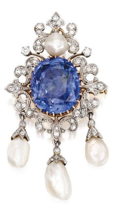 An Antique Platinum, Gold, Sapphire, Diamond and Pearl Pendant-Brooch, Circa 1900. Centring an oval-shaped sapphire weighing 22.24 carats, framed by scrollwork flourishes set with old mine and old European-cut diamonds, accented by four variously-shaped pearls. #antique #brooch