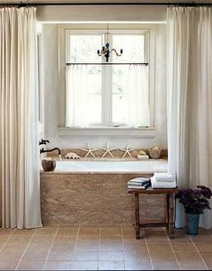 frame in tub with drapes; love the small table for book, drink, ipad, etc. vase with flowers