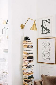 white book stand with gold wall light overhead. / sfgirlbybay