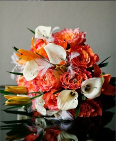 Free spirit roses, orange asiatic lilies and calla lilies with Palm leaves .Designed by Lilypots of Lake Geneva.