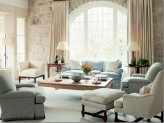 neutral linen draperies hung at ceiling, soft color transition to walls: light creams, blues, greens with dark wood