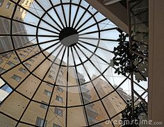 Looking up though a glass, domed roof to a tall building beyond.