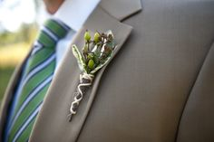 Crisp and clean look on this groom. Accompanied by a boutonniere of hypericum berry, this greige colored suit, with a hint of olive looks awesome paired with this green and blue stripped tie.  Photo Credit: Shawna Herring Photography