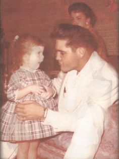 Elvis at Eddie Fadal's home, he's playing with Eddie's daughter