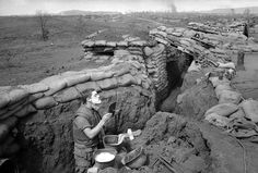 Marine Lance Cpl. Roland Ball of Tacoma, Washington, wearing his flak vest, starts the day off with a shave in a trench at the Khe Sanh base in Vietnam on March 5, 1968, which was surrounded by North Vietnamese regulars. Ball uses a helmet as a sink and a rear view mirror taken from a military vehicle.