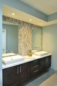 glass tile backsplash behind bathroom mirrors