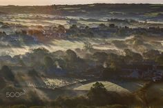 The Play Of Light And Mist - So this morning, I made my early morning way to a little village in the heart of Dorset named Corfe. It hosts a beautiful idyllic little street, flanked by a pair of hills and an 11th century castle. This castle, which is just out of view in this image, was rebuild shortly after William the Conquerers invasion of southern England.  It was upon one of the two aforementioned hills that I set up to take this image. Id arrived shortly before 6am and had sat in…