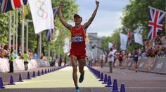 Chen Ding of China celebrates as he crosses the finish line to take gold during the men's 20km Race Walk