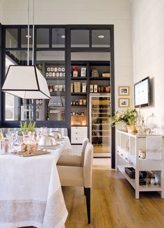 """""""Restaurant-style"""" kitchen with a glass paneled wall and an adjoining dining area with a banquette. Via Blog de Damask et Dentelle."""