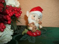 """Very cute nicely painted Elf figurine Vintage late 1960's -early 1970's Homco figurine Hand painted ceramic bisque Red Santa hat and pants, green shirt and boots VERY cute Santa-like face with white beard and pointy ears Toy Maker is holding a toy train and a mallet Marked with gold Homco label and model number 5406 3 3/4"""" h x 3 1/4"""" l x 2 1/4"""" w No known flaws, lovely condition"""