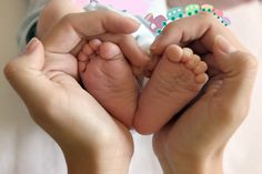 hold baby's feet in heart shaped hands