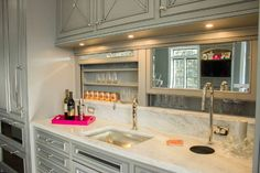 This kitchen bar has remote-controlled retracting mirrored doors where glassware is stored. Above, a bar sink and a sleek, concealed Top Brewer coffeemaker is placed on an elegant marble countertop. Lori Wiles Design.