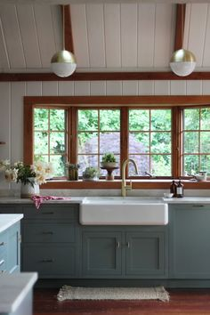 White farmhouse sink with blue/green painted cabinets and light counters.