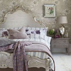 Playful and elegant mixture of vintage and contemporary. Rustic and lovely. Sassy touches of lavender and purple in this beautiful bedroom. Huge white headboard and matching footboard. Delicate wallpaper. Focal silver lamp. Fun purple/plum phone. Cozy blankets.