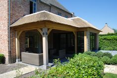 Overdekt terras met uitbreiding van de keuken. voorzien van rieten dak en deels een plat dak.