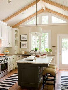 cozinha aberta, em tons neutros, com destaque para a ilha em madeira escura, e tapetes geométricos
