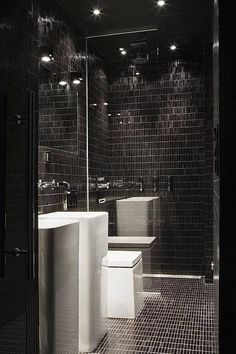 Moody black tiles work with these halogens. The white bathroom pieces stand out as a result.