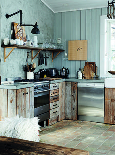 Stylish rustic Norwegian ski chalet kitchen with reclaimed kitchen units, stainless steel appliances, tiled floor and concrete kitchen worktops.