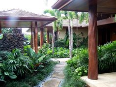 Private Residence, flagstone & river rock path surrounded by lush, tropical green foliage