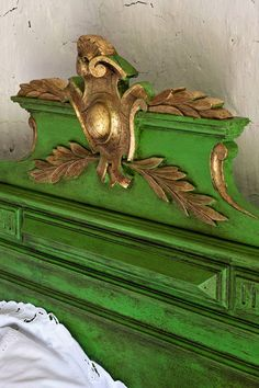 This beautiful piece was finished by Annie Sloan. She used Antibes Green Chalk Paint® on an old French bed with clear and dark wax. Annie also gilded the neo-classical shield and laurel leaves as the perfect accent!