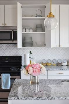 Our Best Renovation Decisions, Part I - white and gold modern kitchen, arabesque tile backsplash, Luna Pearl granite countertops, IKEA cabinets