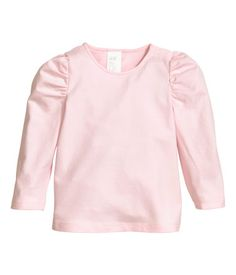 Top in soft cotton jersey. Long sleeves with decorative gathers. Snap fastener at one shoulder.
