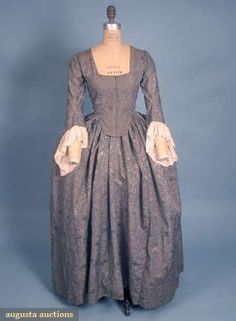 BLUE SILK BROCADE DRESS, c. 1775-1790, England. Steel blue ground w/ meandering allover small floral pattern in French blue & ivory, 3/4 sleeves w/ attached Dresden work lace engageants, bodice w/ CF lacing & lined w/ dark taupe homespun linen, skirt & sleeves lined in white & blue windowpane linen. Augusta Auctions