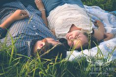 Engagement session of couple pose posed lying in grass on a quilt. romantic, southern, cute, smiling. Photo taken by heather la'rie photography in Chickamauga, ga