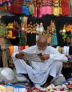 Vendor reads newspaper in Pakistan market