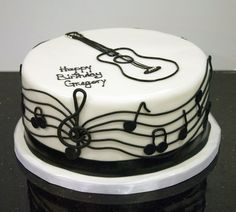 A black and white musical/guitar cake for a musician's birthday. Created by…