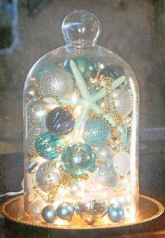 DIY coastal Christmas decor idea- aqua colored christmas balls, some shells or painted starfish, plus strung beads for some extra bling. Add some mini white twinkle lights and place inside a glass cloche on a flat dish.