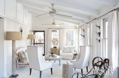 A wall of windows allows natural light to bathe every corner of this light and airy living room. Artist and owner Dawne Raulet Hall treated the formerly drab space to a monochromatic makeover, dressing the walls in white and infusing the space with a stylish mix of sophistication and charm. The antique sofa, with remnants of red velvet, was purchased at Boxwoods. She found the 1800's twig rocker at Scott Antique Markets. Column lamps and wingback chairs, Huff Harrington Home.