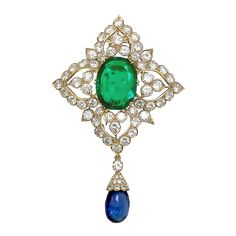 A thirteen carat oval-shaped Old-Mine (Muzo) Colombian Emerald suspended with a detachable fifteen carat Ceylon Sapphire Briolette Drop in a Van Cleef & Arpels Brooch, accented with diamonds and mounted in 18kt Yellow Gold.