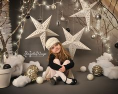 Child Sitting in Winter Tree Star Scene - A little girl is sitting in a winter wonderland setip with trees, hanging stars and christmas lights around the background for a season or holiday concept. Digital Backdrop available for sale on my Etsy store: https://www.etsy.com/shop/HaywireMedia