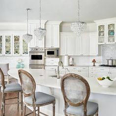 Loving the combination of rustic and glamorous in this kitchen! It features pretty Crystorama Lighting Calyspo pendants at the island. Glass Front Cabinets, Upper Cabinets, Ideal Home Show, High Back Chairs, Mini Chandelier, Top Interior Designers, Round Dining Table, New Kitchen, Kitchen Ideas