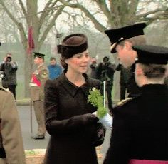"""""""Kate handing Prince William his shamrocks during the St Patrick's Day Parade."""""""