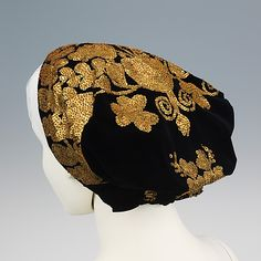 Hungarian Hat  1900 - 1920  The very elaborate sequin embroidery of this hat makes for a grand appearance. The central motif is an adaptation of the traditional tree of life. The solid gold effect of the overlapping sequins is set off by the black velvet ground, with the amber beads creating an interesting textural element.