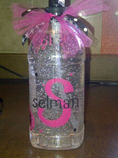 """a HUGE germ sanitizer bottle at Sams (Remove all labels with vinegar and toothpaste-to remove adhesives),  black and hot pink vinyl for the cricut.  Set the back """"S"""" at a 4"""" on the cricut, then applied the whole name in 1"""" setting over the top of the """"S"""".  Gift for teacher.  add tulle/ribbon to the top and personalized the back."""