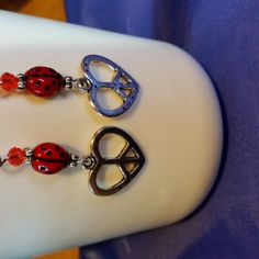 An adorable pressed bead of a ladybug adorns this peace sign shaped like a heart.