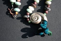 glass and metal ammonite necklace by krixbeeble on Etsy. perfect for summer :]