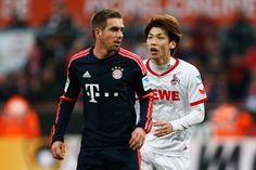 Yuya Osako (R)of koeln and Philipp Lahm of Bayern Muenchen look on during the Bundesliga match between 1. FC Koeln and FC Bayern Muenchen held at RheinEnergieStadion on March 19, 2016 in Cologne, Germany.