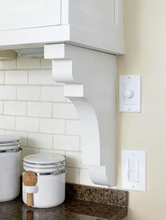 Corbels under cabinets for desk area in laundry room-creates a visual break for tile to stop for a nice transition from folding area to desk
